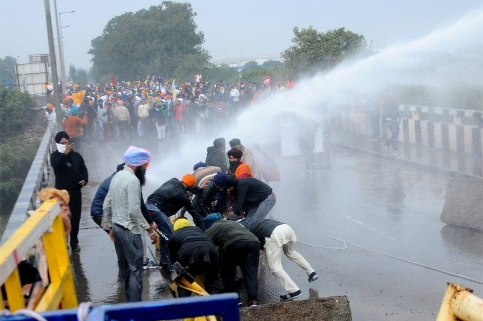 Water cannon is used against farmers by Haryana state police as they try to remove concrete barricades installed by police to stop them from entering Haryana as they march towards New Delhi to protest against new farm laws,