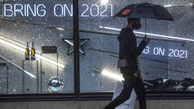 A man with an umbrella is seen walking past a shop display with a sign reading 'Bring on 2021' on December 14, 2020 in London