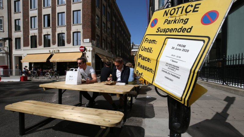 People eat lunch at tables and benches placed in the roadway adjacent to a suspended parking bay in Golden Square, Soho
