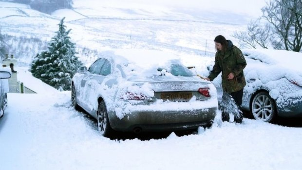 A motorist clears heavy overnight snow from a car in Carrshield in the Pennines, near Hexham in Northumberland