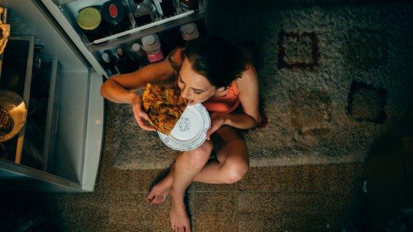 Mujer comiendo con la puerta del frigorífico abierta.