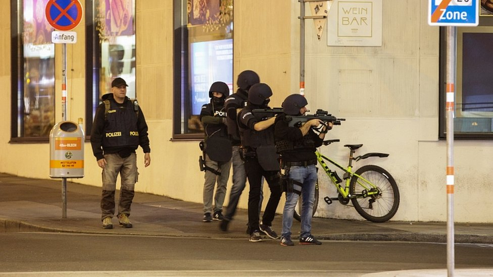 Police officers aim their weapons on the corner of a street after exchanges of gunfire in Vienna, Austria November 2, 202