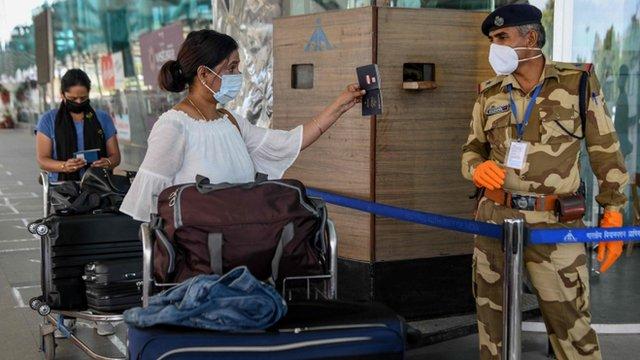 Una mujer le muestra el pasaporte a un guardia de seguridad en un aeropuerto