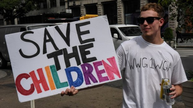 "A person wears a t-shirt with the anagram WWG1WGA, the QAnon slogan, while participating in a ""save the children"" march and rally in New York City, New York, U.S. August 12, 2020"