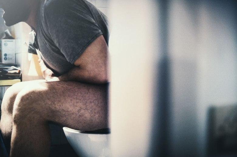 Hombre con dolor estomacal sentado en el inodoro