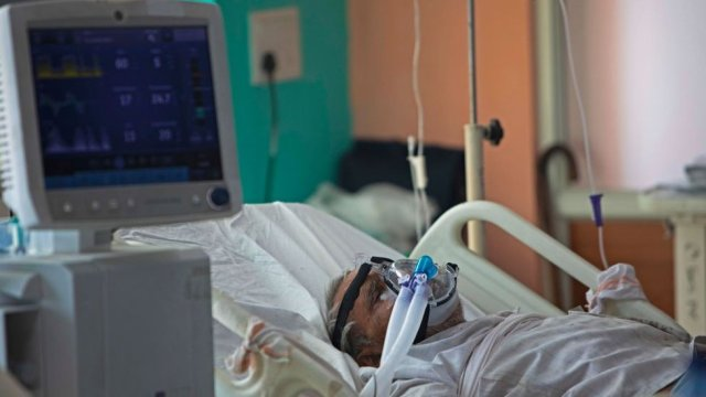 In this photograph taken on July 15, 2020 a COVID-19 coronavirus patient lies on a bed at the Intensive Care Unit of the Sharda Hospital, in Greater Noida