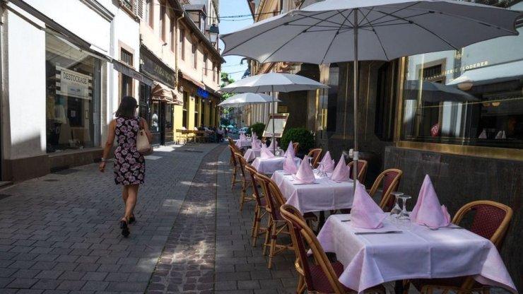 A woman in a dress walks past an empty restaurant in Strasbourg, eastern France, in June 2020
