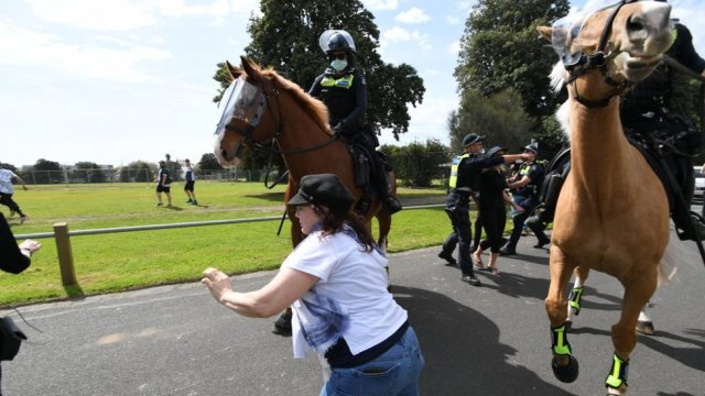 Police try to intercept protesters during an anti-lockdown protest in Melbourne, Australia, 19 September 2020