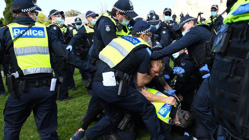 police grapple a protester