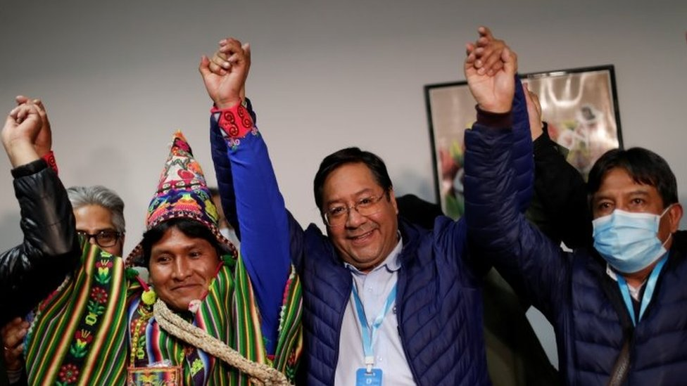 Presidential candidate Luis Arce of the Movement to Socialism party (MAS) reacts next to vice presidential candidate David Choquehuanca, who wears a protective face mask, after addressing the media during the presidential election in La Paz, Bolivia, October 19, 2020.
