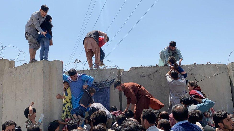 Personas escalando el muro que encierra el Aeropuerto Internacional Hamid Karzai