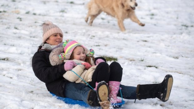 Lizzy and daughter Connie, 6, are chased down a snow covered hill by their golden retriever Pippa in a park in Newcastle-under-Lyme, Staffordshire.