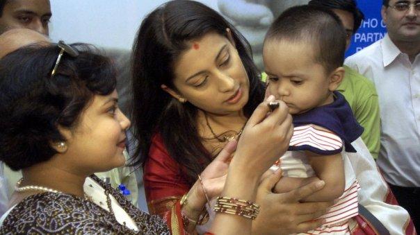 Mujer alimentando a niño que carga otra mujer