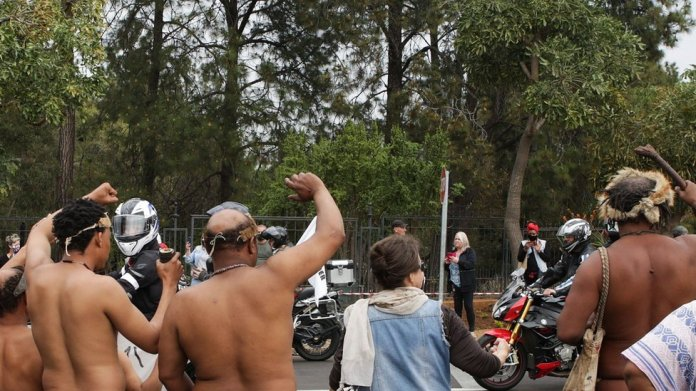 KhoiSan people wave in solidarity with Bikers United Against Farm Murders and Racism as they ride past the Union Buildings in Pretoria, on August 29, 2020