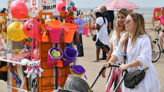 Two women walk past a stall selling toys on a beach