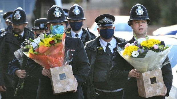 Police officers holding flowers