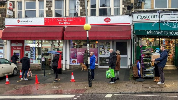 People queue for a post office on Sandy park Road, Bristol