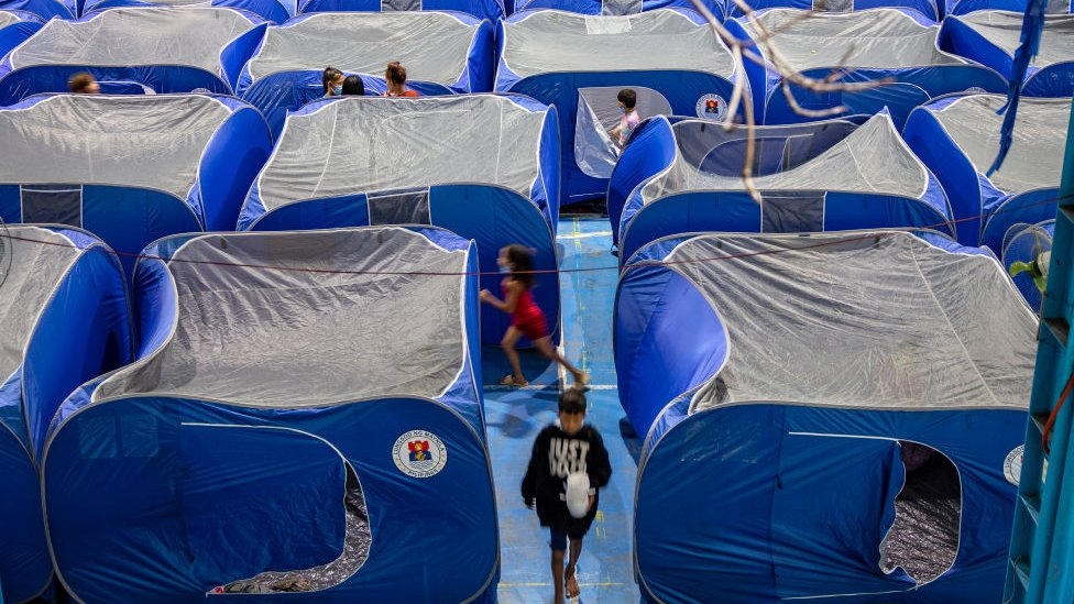 Filipinos take shelter in tents inside a school gymnasium converted into an evacuation centre before Typhoon Goni hits on November 1, 2020 in Manila, Philippines