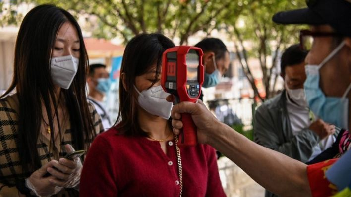 A worker wearing a face mask checks passengers body temperatures and a health code on their phones before they take a taxi after arriving at Hankou railway station in Wuhan, Hubei Province on May 12, 2020.