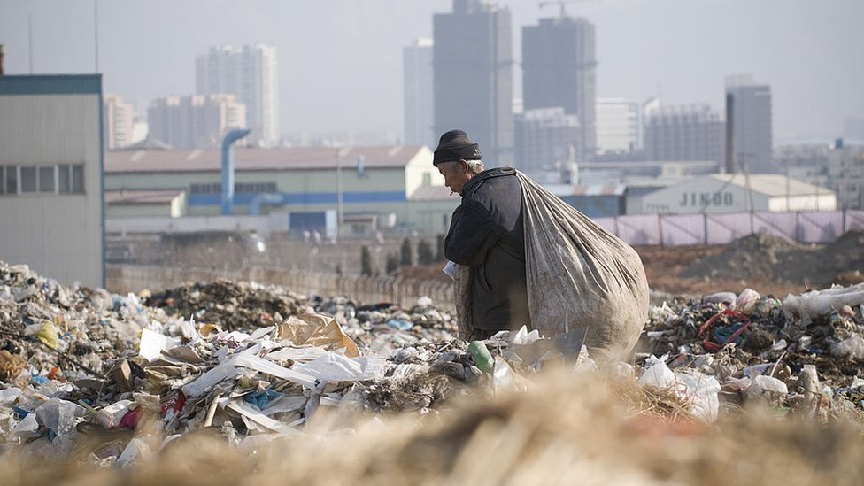 An elderly male migrant worker carries a large bag of plastic bottles he had collected at the Dalian Jinzhou garbage dump.