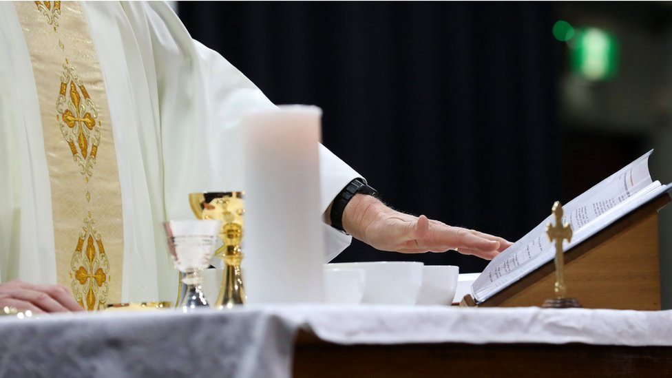 Padre reza la misa