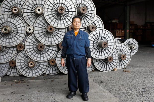 A denim maker stands in a factory
