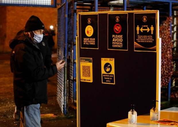 A Luton Town fan wearing a protective face mask stands outside the stadium before the match