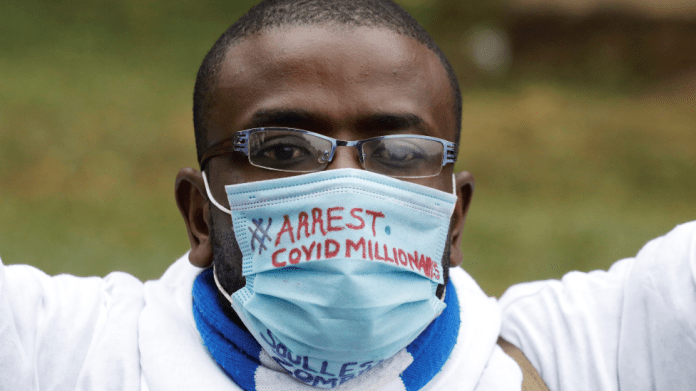 """A Kenyan man wearing a mask with the words """"arrest Covid millionaires"""" written on it - August 2020"""