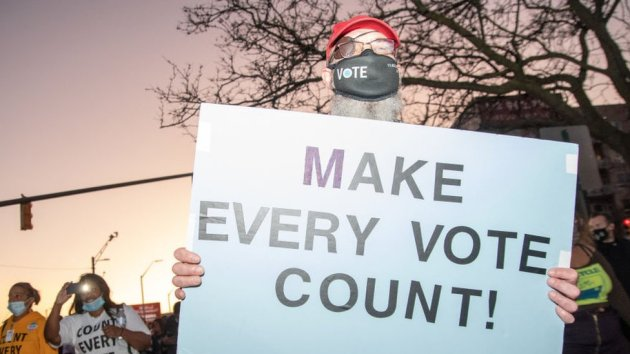 """A protester in Michigan holds up a sign that says """"Make Every Vote Count"""""""