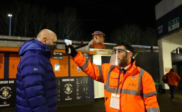 A Luton Town fan has their temperature taken whilst wearing a face mask