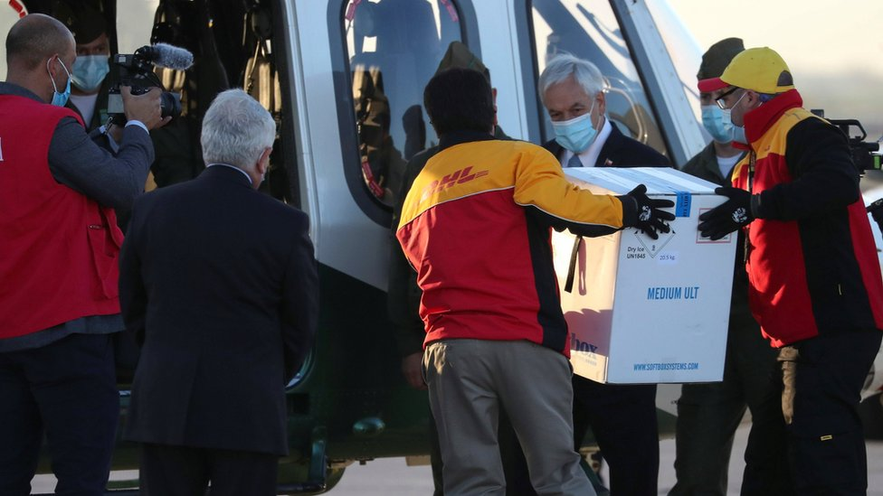 Chile's President Sebastián Piñera (centre-right) looks as workers carry the first batch of the Pfizer-BioNTech vaccine to a helicopter at Santiago's airport. Photo: 24 December 2020