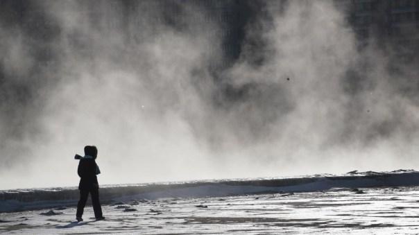 Una mujer caminando cerca del lago Michigan congelado.
