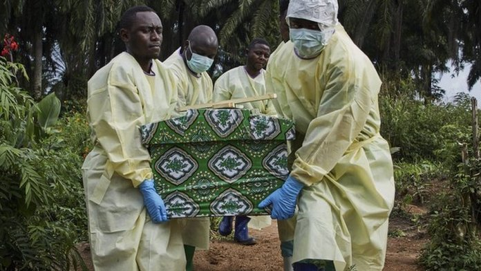Ebola workers carrying a coffin