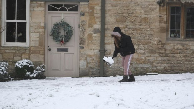 A woman clears snow from pathway in Burford, West Oxfordshire.