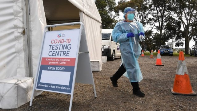 A healthcare working in protective gear works at a COVID-19 testing facility in Melbourne, Victoria, Australia, 18 September 2020