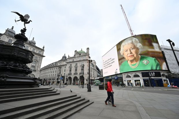 A billboard screen in Picadilly Circus shows an image of the Queen