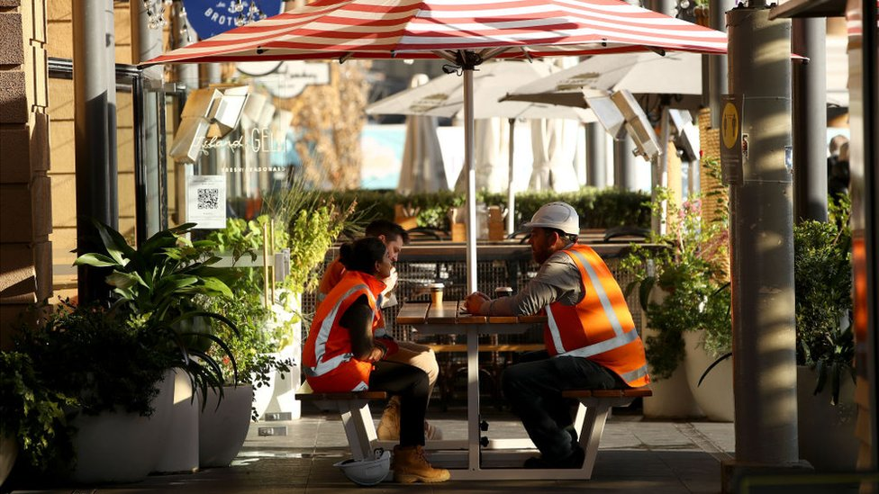 Construction workers sitting together, having a coffee break