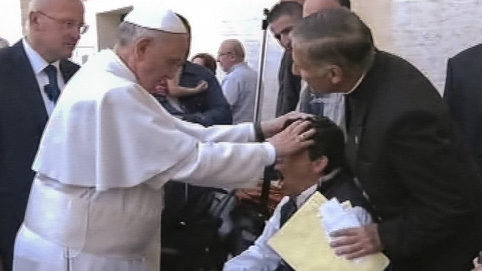 Captura de pantalla de televisión que muestra al papa poniendo sus manos sobre la cabeza de un joven durante una misa de domingo.