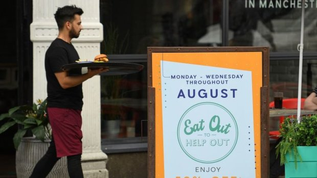 Waiter walking past an ''eat out to help out'' sign