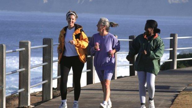 Tres mujeres andando con ritmo rápido por un embarcadero.