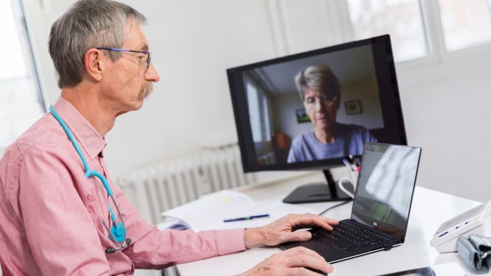 Doctor holds a medical teleconsultation with an elderly female patient.