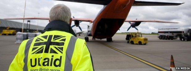 A Dfid employee wearing a UK aid hi-vis heads towards a plane