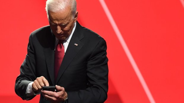 Joe Biden looks down at his smartphone while standing against a giant stage drop background in bright red