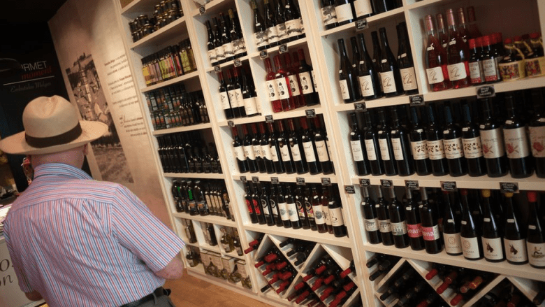 An elderly man looks at bottles of wine displayed inside a store