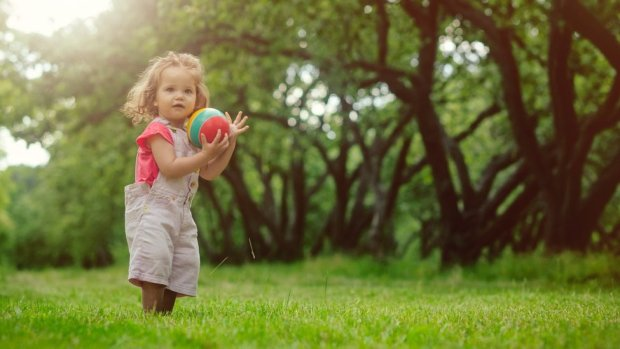Small girl with ball in field