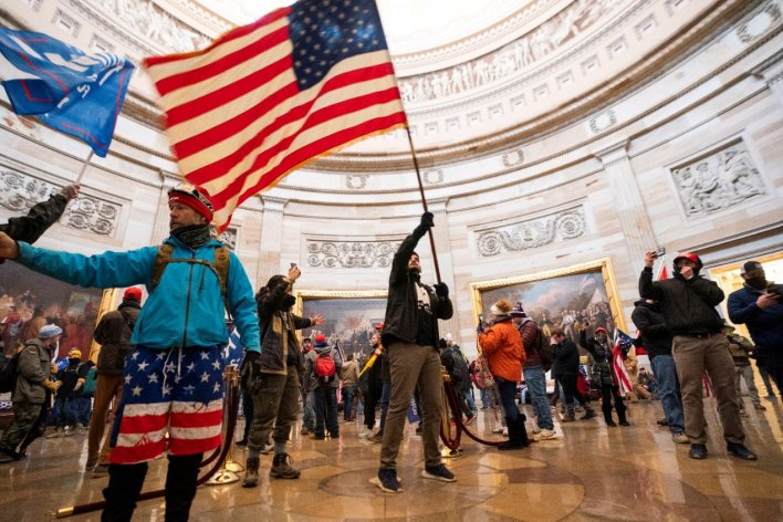Protesters fill the Rotunda of the US Capitol building waving a US flag