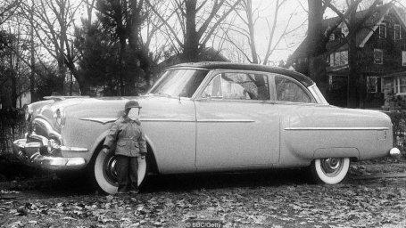 Niño frente a un automóvil.