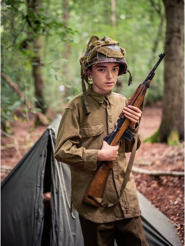 A boy stands in the woods dressed as a solider from World War Two