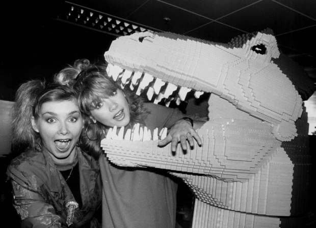 Two singers pose with a Lego dinosaur