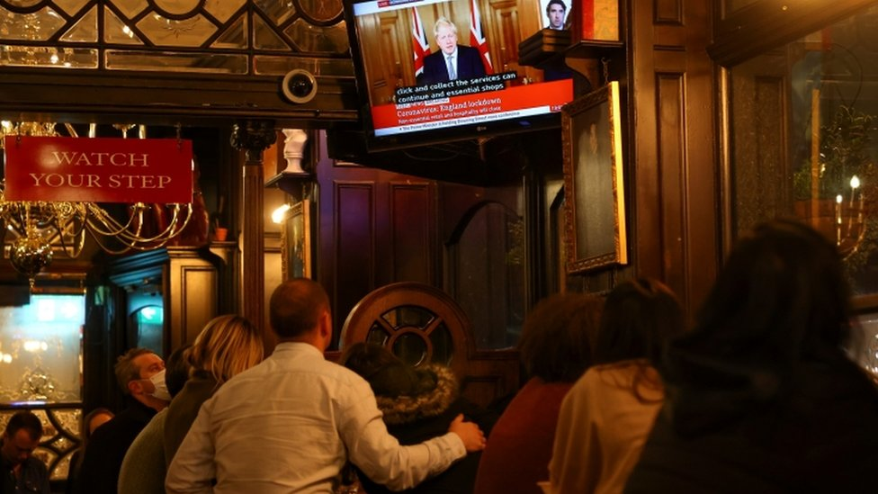 People inside a pub in Westminster watching Boris Johnson announce new lockdown measures